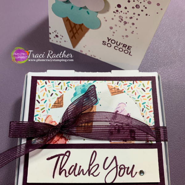 Small white box decorated with ice cream cones and burgundy ribbon